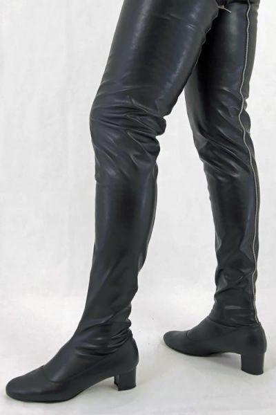 Schrittlanger schwarzer Stretchkunstleder Stiefel im Stil der 60er Jahre mit durchgehendem Reißverschluss hinten.